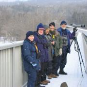 Picture of Bill and Heather with friends bird watching from a snowy bridge