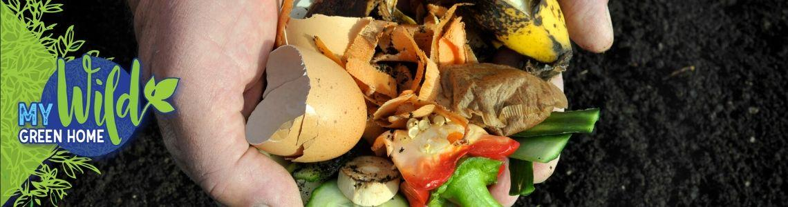 A handful of organic waste, including egg shells, banana peels, and vegetable scraps are held over a pile of dark brown dirt.