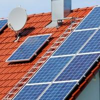 Image shows a house rooftop with solar panels on it.