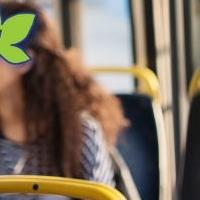 A close up of a woman texting while commuting on a city bus.