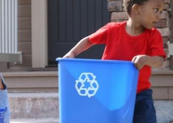 Three children are holding recycle bins and sorting their recyclable materials, outside of their house.