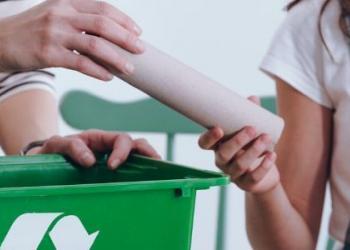 3 children help a parent to sort paper towel rolls into a recycling bin.