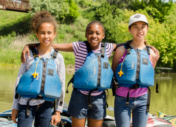 Three children stand facing the camera. They are wearing PFDs and smiling. In the background we see colourful kayaks on the shore of beach, the Rouge River, and green leafy foliage in the distance.