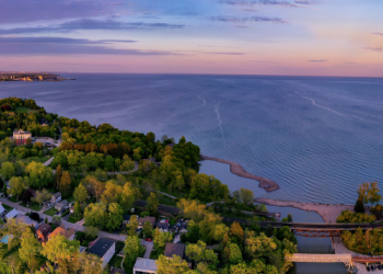 An aerial shot at sunrise looking south over Lake Ontario the southern extent of Rouge National Urban Park. The sky is a mix of light pink, orange, and blues and we can see the beach and surrounding area at the bottom.