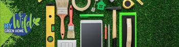 A flat lay of hardware tools, pencils, paintbrushes, an iPad, and tape on grass